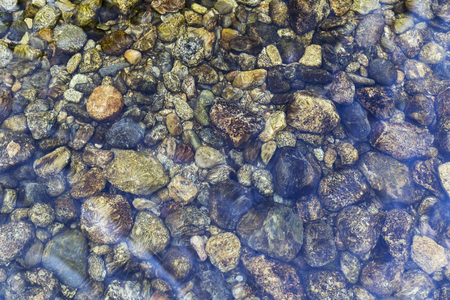 round stones at the bottom of the river under a crystal clear water Stock Photo