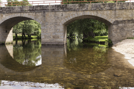 Old stone bridge for a road that crosses a small dam of a river Stock Photo