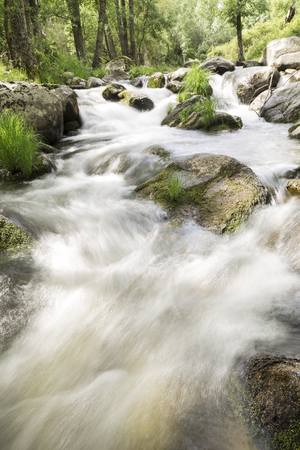 water running down rapids of a river with stones photographed at low speed to give silk effect Stock Photo
