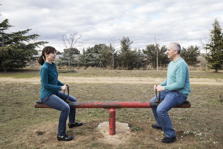 woman and man mounted on a seesaw representing gender equality