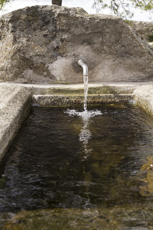 Stone fountain with an iron spout with water running