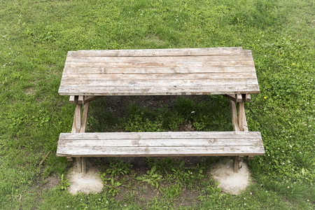 wooden table with benches for picnic in the shade on green grass on a spring day Stock Photo