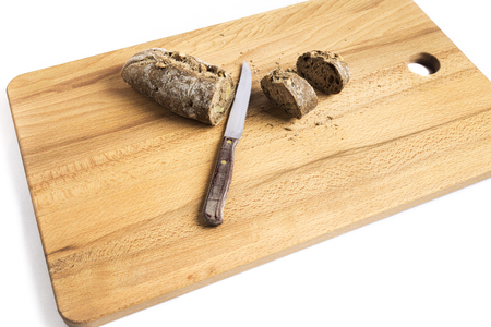 small bar of wholemeal bread with freshly made walnuts next to a knife on a wooden board