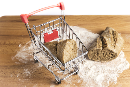 small loaf of whole wheat bread elongated in a small shopping cart on flour on a wooden table