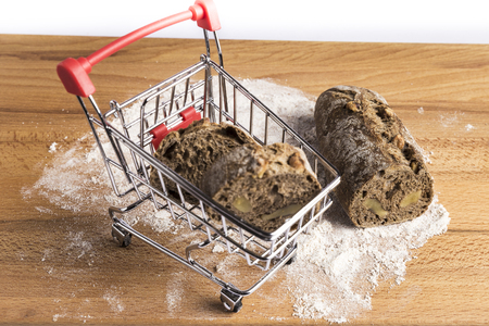 small bar of wholemeal bread with nuts freshly made in a small shopping cart on flour on a wooden table