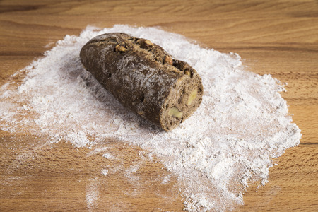 small bar of wholemeal bread with freshly made walnuts next to some ingredients on a wooden table Stock Photo