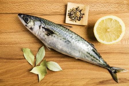 mackerel fresh fish next to some laurel leaves, a piece of lemon and some spices on a wooden table prepared for cooking