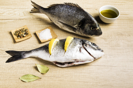 Two fresh fish Dorada with bay leaves, some pieces of lemon, a bowl of oil and some spices on a wooden table prepared for cooking