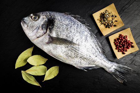 Dorada fresh fish with bay leaves and spices on a black slate table prepared for cooking