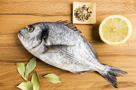 Dorada fresh fish next to bay leaves, a piece of lemon and some spices on a wooden table prepared for cooking