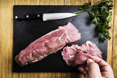 mans hands splitting a pork tenderloin with a knife next to some parsley branches on a black slate griddle on a wooden table