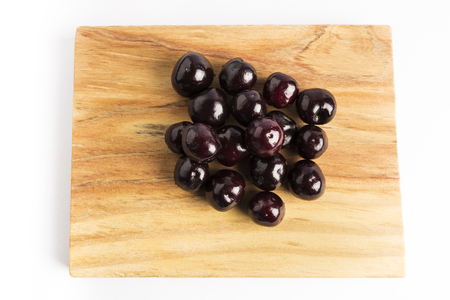 group of fresh red cherries on a wooden board on a white background