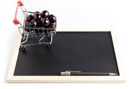 group of fresh red cherries in a small shopping cart next to a pen on a black chalkboard with a white background Stock Photo