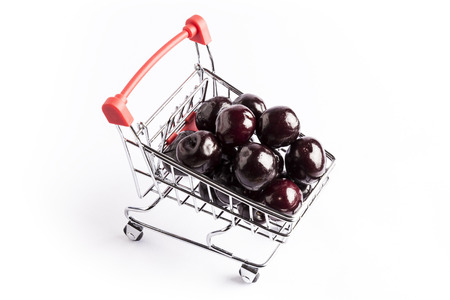 group of fresh red cherries in a small shopping cart on a white background