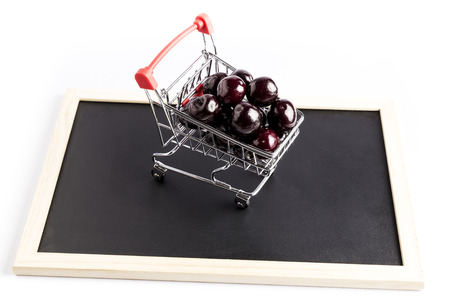 group of fresh red cherries in a small shopping cart on a black chalkboard with a white background