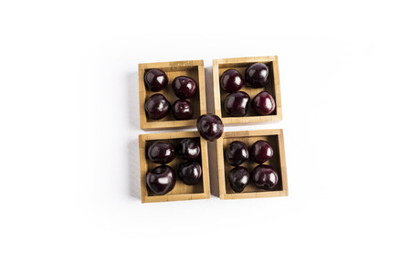 group of fresh red cherries in a wooden square bowls on a white background