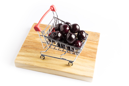 group of fresh red cherries in a small shopping cart on a wooden board with a white background