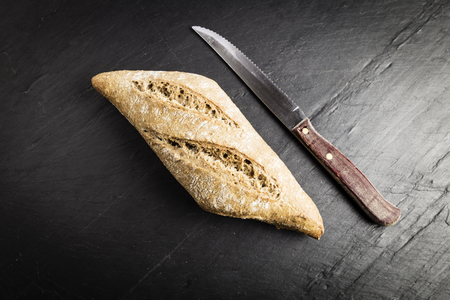 small loaf of whole wheat flour elongated next to a knife on a black slate table Stock Photo
