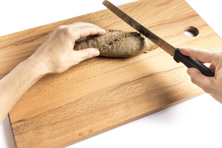 woman cutting a small loaf of whole wheat bread on a wooden board with a knife