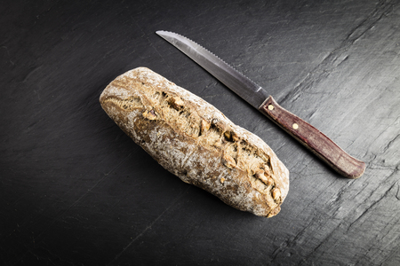 small whole-grain bread stick with freshly made walnuts next to a knife on a black slate table