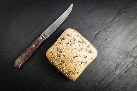 Bread with linseed, oats and sesame seeds next to a knife on a black chalkboard Stock Photo