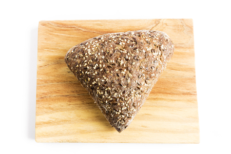 Triangle-shaped wholemeal bread with flax seeds, oats and sesame on a wooden board Stock Photo