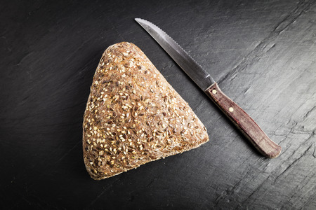 Integral bread in the form of a triangle with linseed, oats and sesame seeds next to a knife on a black slate table