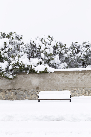 lonely wooden bench filled with snow on a snowy street next to a park Stock Photo