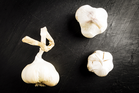 three heads of white garlics on a black slate table Stock Photo