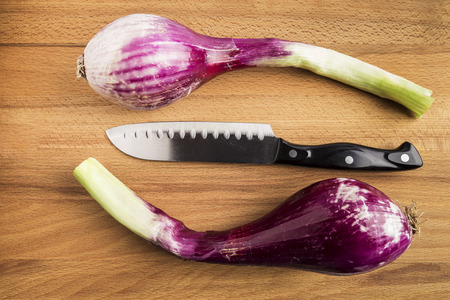 two fresh whole purple chives next to a knife on a black slate table Stock Photo