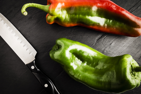 one fresh green and red pepper next to a knife on a black slate table
