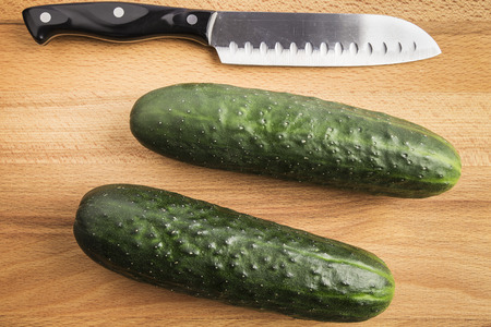 two whole green cucumbers next to a knife on a wooden table