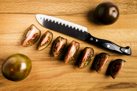 dark red whole kumato tomatoes and cut together with a knife on a wooden table Stock Photo
