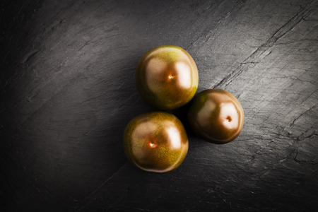 group of dark red kumato tomatoes on a black slate table Stock Photo