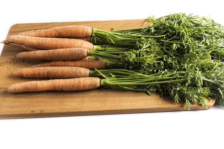 bunch of carrots with green leaves on a wooden board