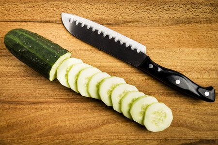 whole and cut green cucumbers next to a knife on a wooden table