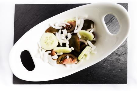 salad of tomato, onion and cucumber in a white bowl on a black slate table
