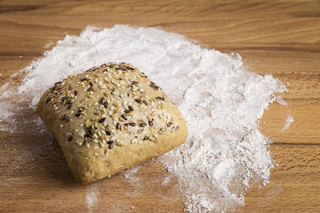 Bread with linseed, oats and sesame seeds next to some ingredients on a wooden table Stock Photo