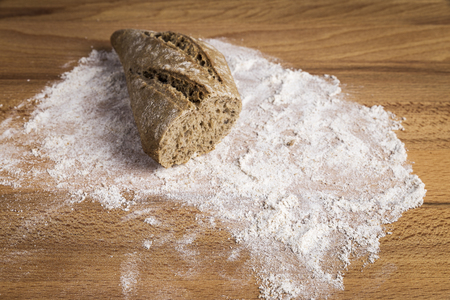 small loaf of whole wheat bread elongated on flour on a wooden table