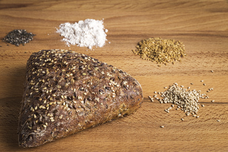 Triangle-shaped wholemeal bread with linseed, oats and sesame seeds next to some ingredients on a wooden table