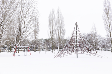 snowy park with swings and trees, empty on a cold winter day