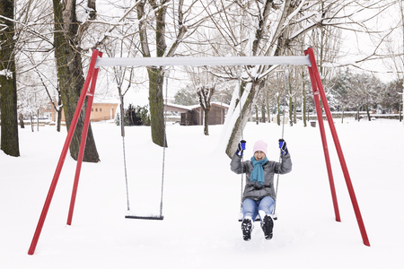 woman swinging and having fun on a swing in a snowy park on a cold winter day