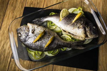 two Dorada fish cooked in the oven with lemon, onion and green pimento in a glass dish on a black slate tray