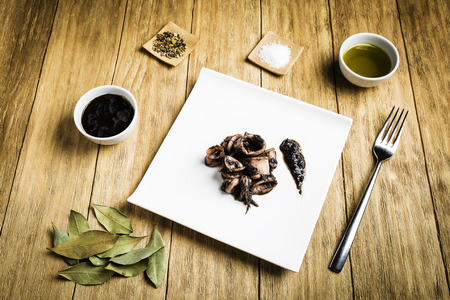 squid cooked on a white plate with a fork, a bowl with ink, a bowl of oil, salt, spices and bay leaves on a wooden board