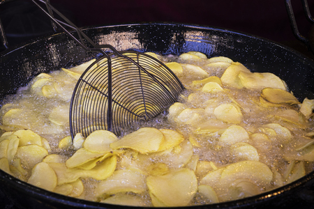 frying chips in a black pan with a lot of boiling oil in a restaurant Zdjęcie Seryjne