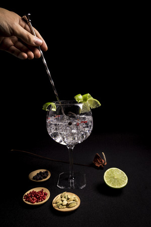 barman preparing a gin and tonic cocktail on a black background next to his ingredients