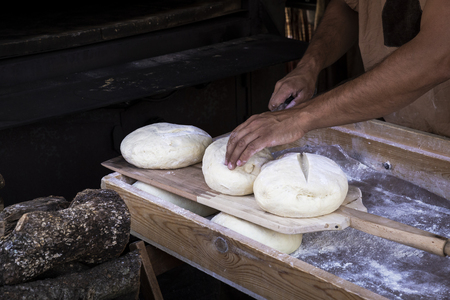 man putting bread dough in the wood-fired oven at a market stall