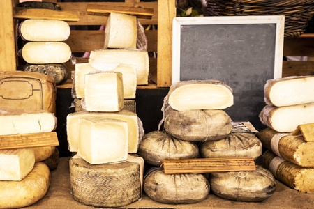 Assorted pieces of cheese for sale at a traditional market stall Stock Photo