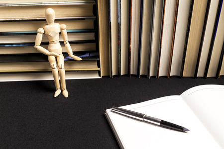 wooden dummy next to a pen on a blank book next to a background of books on a black tablecloth