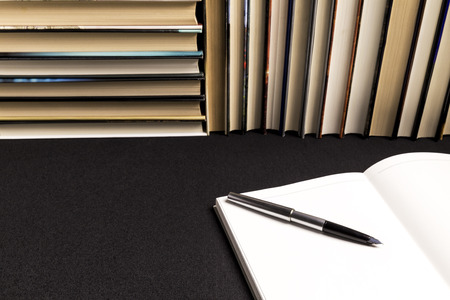pen on a blank book next to a background of books on a black tablecloth